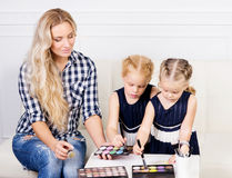 Young mother with two beautiful daughters with make-up palette. Stock Images