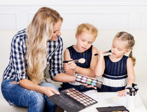 Young mother with two beautiful daughters with make-up palette. Royalty Free Stock Photo