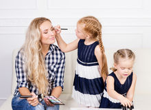Young mother with two beautiful daughters with make-up palette. Royalty Free Stock Photography