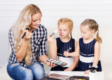 Young mother with two beautiful daughters with make-up palette. Stock Photos