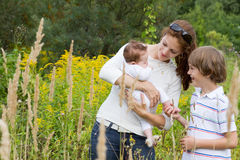 Young mother with two children in a yellow flower field Stock Photo