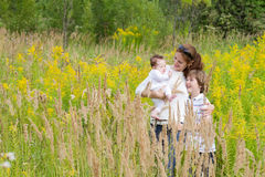 Young mother with two children in a yellow flower field. Beautiful young mother with two children in a yellow flower field Stock Photography