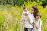 Young mother with two children in a yellow flower field Stock Photos