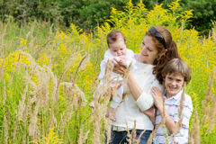 Young mother with two children in a yellow flower field Royalty Free Stock Images