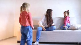 Young mother with two daughters plays on sofa in living room. Beautiful dark-haired young mother sitting on couch in living room and playing with two small stock video footage