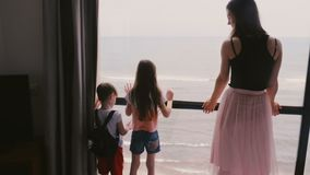 Young mother with two happy excited little kids together at large apartment window watching amazing sea view slow motion