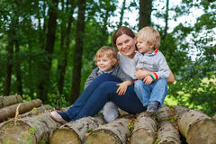 Young mother and two little boys having fun in summer forest. Stock Photo