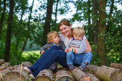 Young mother and two little boys having fun in summer forest. Stock Image