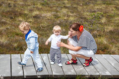 Young mother and two little boys in summer nature park royalty free stock image