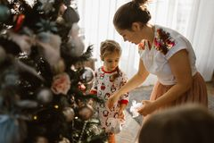 Young mother with two little daughters in pajamas decorate a New Year`s tree in the cozy room with with big light window stock image