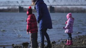 A young mother and two little daughters are walking on the city embankment of the river. Slow motion. A young mother and two little daughters are walking on the stock footage