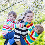 Young mother and two little twins boys having fun in blooming ga royalty free stock images