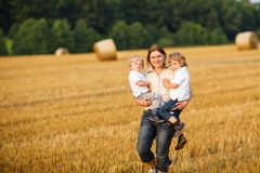 Young mother and two little twins boys having fun on yellow hay Royalty Free Stock Photography