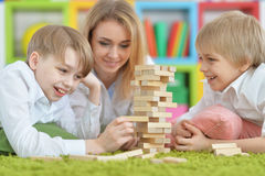 Young mother and two sons playing. Beautiful young mother and two sons playing with wooden blocks stock images