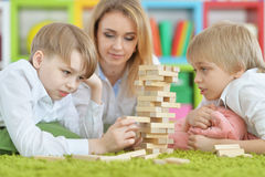 Young mother and two sons playing. Beautiful young mother and two sons playing with wooden blocks Stock Photography