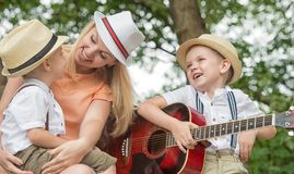 Young mother and two sons are resting in the woods,singing songs with a guitar. Young mother and two sons are resting in the woods stock images
