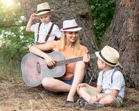 Young mother and two sons are resting in the woods,singing songs with a guitar. Young mother and two sons are resting in the woods stock photography