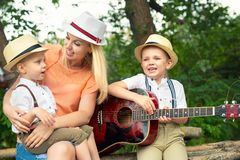 Young mother and two sons are resting in the woods,singing songs with a guitar. Young mother and two sons are resting stock photos