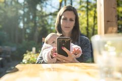 Young mother using mobile phone while with her daughter. Young mother using her mobile phone as she is sitting outside in a coffee holding her baby daughter royalty free stock image