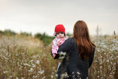 Young mother walking away holding her baby. Royalty Free Stock Photo