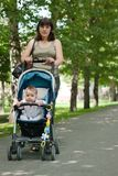 A young mother walking with a baby carriage Royalty Free Stock Photo