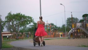Young mother walking baby carriage in city park standing wearing bright red dress with naked legs stock video footage