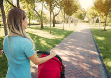 Young mother walking with baby carriage in the park Stock Photo
