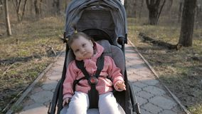 Young mother walking with a baby girl in stroller in the park stock footage