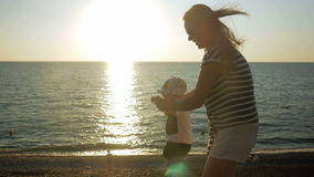 Young mother walking with cute baby on the oceanfront at sunset. The baby is still very poor, and my mother runs it. Holds. The concept of the first steps in stock video footage