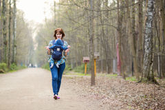 Young mother walking in forest with her baby stock images