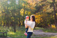 Young mother walking with her baby in an autumn Stock Photo