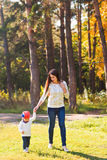 Young mother walking with her baby in an autumn Royalty Free Stock Photos