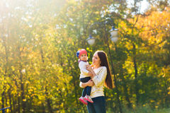 Young mother walking with her baby in an autumn Stock Photos