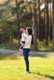 Young mother walking with her baby in an autumn Stock Images