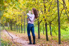 Young mother walking with her baby in autumn park Royalty Free Stock Photos
