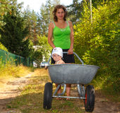 Young mother walking with her baby. Baby sits in barrow Royalty Free Stock Images
