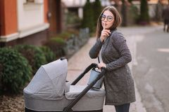 Young mother walking with her baby in stroller and putting finger up to lips and saying shh. Mom gesturing silence.  stock photo