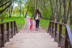 Young mother walking with her little daughter in Stock Photo