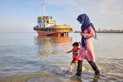 Young mother walking with her son on shores Persian Gulf. Stock Photo