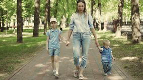 A young mother is walking in a park with children. Slow motion. stock footage