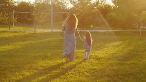 A young mother is walking in the park at sunset. A happy young mother is walking in the park at sunset stock video footage