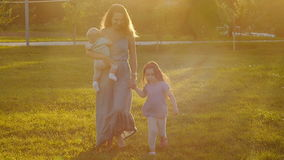 A young mother is walking in the park at sunset. A happy young mother is walking in the park at sunset stock footage
