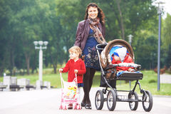 Young mother walking with pram and kids in park. Smiling young mother walking with daughter outdoors in a spring park pushing pram. Little boy in stroller Stock Photography