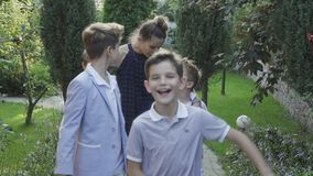 Young mother walks with her sons at the backyard of country house stock video footage