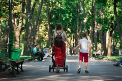 Young Mother Walks In Park With Baby And Older Son. Mom Holds Son`s Hand. Motherhood Concept Royalty Free Stock Images