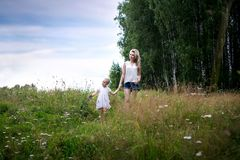 A young mother walks through a meadow with a little girl. Summer day, wildflowers, birch. Mom and daughter blonde stock images