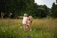 A young mother walks through a meadow with a little girl. Summer day, wildflowers, birch royalty free stock image