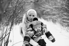 A young mother walks on a winter day with a baby in her arms Stock Image