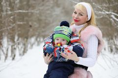 Young mother walks on a winter day with a baby in her arms in th Royalty Free Stock Photos