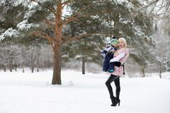 Young mother walks on a winter day with a baby in her arms in th Stock Photography